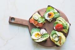与菜,鸡蛋,鲕梨,蕃茄,在轻的大理石桌上的黑麦面包的不同的三明治 顶面vew 党的开胃菜 平的l 免版税图库摄影