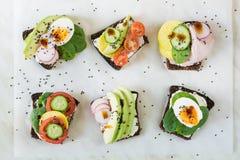 与菜,鸡蛋,鲕梨,蕃茄,在轻的大理石桌上的黑麦面包的不同的三明治 顶面vew 党的开胃菜 平的l 图库摄影