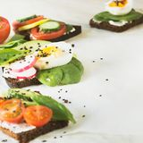 与菜,鸡蛋,鲕梨,蕃茄,在轻的大理石桌上的黑麦面包的夏天三明治 党的开胃菜 关闭 图库摄影