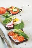与菜,鸡蛋,鲕梨,蕃茄,在轻的大理石桌上的黑麦面包的夏天三明治 党的开胃菜 关闭 库存图片