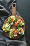 与菜,鸡蛋,鲕梨,蕃茄,在黑黑板背景的黑麦面包的不同的三明治 顶面vew 部分的开胃菜 图库摄影