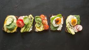 与菜,鸡蛋,鲕梨,蕃茄,在黑黑板背景的黑麦面包的不同的三明治 顶面vew 免版税库存照片