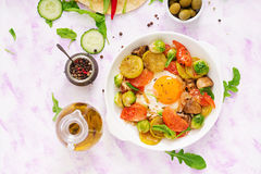 与菜- shakshuka和新鲜的黄瓜、西瓜萝卜和芝麻菜的煎蛋 图库摄影