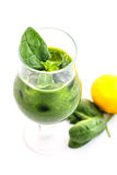 与菠菜叶子和柠檬的新鲜的绿色圆滑的人在白色背景隔绝的玻璃,菠菜,黄瓜,苹果果汁饮料,刺 免版税库存图片