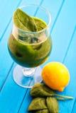 与菠菜叶子和柠檬的新鲜的绿色圆滑的人在蓝色背景,菠菜,黄瓜,苹果果汁饮料,刺的玻璃 免版税库存图片