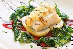 与菠菜叶子的烤鳕鱼。 库存图片