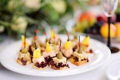 与菠萝和雀跃冠上的可口点心快餐在党或结婚宴会服务 免版税库存照片