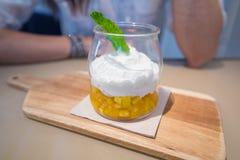 与菠萝大块的酸奶和在玻璃瓶子的薄荷的叶子在woode 免版税库存照片