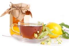 与菩提树蜂蜜瓶子和花的柠檬茶 图库摄影