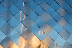 与菱形的老,肮脏铝金属墙壁门面盘区,相似与标度和瓦片 日落的反映 免版税图库摄影