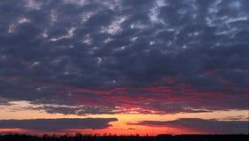 与落日和乌云的晚上风景 免版税库存图片