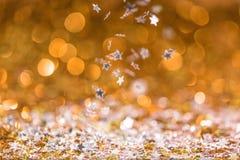 与落的圣诞节纹理金黄和银色发光的五彩纸屑星 库存图片