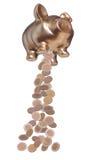 与落的硬币的金黄piggybank 免版税库存照片