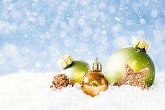 与落的雪的金黄和绿色圣诞节球 免版税库存照片