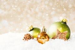 与落的雪的金黄和绿色圣诞节球 库存照片
