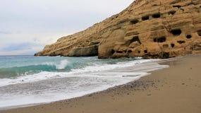 与落矶山脉的Matala小海滩和海在克利特海岛希腊上挥动 图库摄影