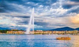 与著名喷气机d ` Eau喷泉和小船的日内瓦地平线在日落 库存图片