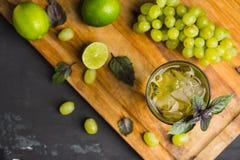与葡萄、石灰和蓬蒿叶子的新鲜的鸡尾酒 免版税库存图片