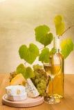 与葡萄和乳酪快餐的白葡萄酒 库存照片