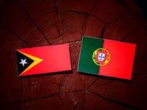与葡萄牙旗子的东帝汶旗子在被隔绝的树桩 库存例证