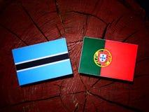 与葡萄牙旗子的博茨瓦纳旗子在被隔绝的树桩 免版税库存照片