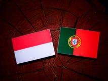 与葡萄牙旗子的印度尼西亚旗子在被隔绝的树桩 库存例证