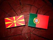 与葡萄牙旗子的马其顿旗子在被隔绝的树桩 库存例证