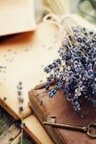 与葡萄酒书、老钥匙和淡紫色的减速火箭的静物画开花,怀乡构成 免版税库存图片