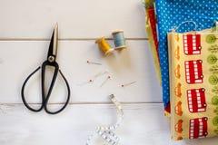 与葡萄酒剪刀、别针、测量的磁带和滚动的棉花螺纹的五颜六色的织品在白色木桌上 库存照片