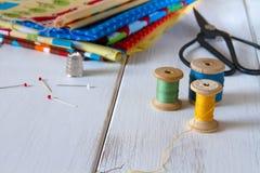 与葡萄酒剪刀、别针、测量的磁带和滚动的棉花螺纹的五颜六色的织品 免版税库存照片