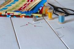 与葡萄酒剪刀、别针、测量的磁带和滚动的棉花螺纹的五颜六色的织品 库存照片