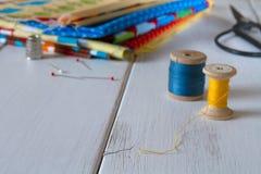 与葡萄酒剪刀、别针、测量的磁带和滚动的棉花螺纹的五颜六色的织品 库存图片