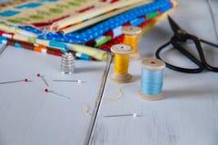 与葡萄酒剪刀、别针、测量的磁带和滚动的棉花螺纹的五颜六色的织品 免版税库存图片