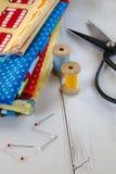 与葡萄酒剪刀、别针、测量的磁带和滚动的棉花螺纹的五颜六色的织品 免版税图库摄影