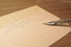 与葡萄酒墨水羽毛的古色古香的明信片 免版税库存照片