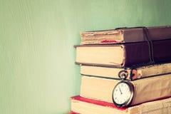 与葡萄酒怀表的旧书在一张木桌上 减速火箭的被过滤的图象 库存图片