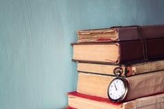 与葡萄酒怀表的旧书在一张木桌上 减速火箭的被过滤的图象 库存照片