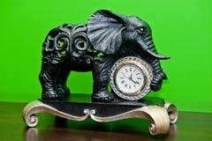 与葡萄酒时钟的古铜色大象在绿色背景 库存照片