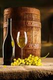 与葡萄酒杯瓶和winegrape的藤构成老桶 库存图片