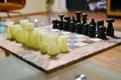 与葡萄酒比赛的减速火箭的阿塞拜疆棋子在木背景计时 首先移动E2 - E4 免版税库存照片
