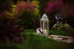 与葡萄酒灯笼和蜡烛台的舒适晚上庭院场面 免版税库存图片
