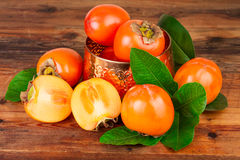 与葡萄酒的柿子上铜在老木头的花瓶 生活仍然东方人 免版税图库摄影