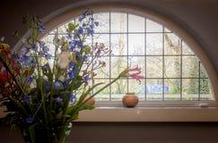 与葡萄酒窗口的五颜六色的花在房子里 库存照片