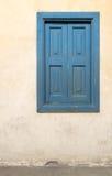 与葡萄酒膏药墙壁的蓝色木窗口 库存图片