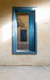 与葡萄酒膏药墙壁的被打开的蓝色木窗口 免版税库存照片