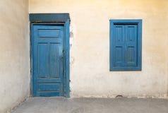 与葡萄酒膏药墙壁的被打开的蓝色木窗口 库存图片