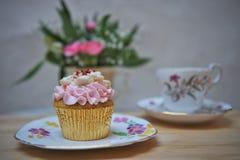 与葡萄酒花卉陶器和杯形蛋糕的下午茶 库存照片