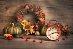 与葡萄酒闹钟的秋天静物画 库存图片
