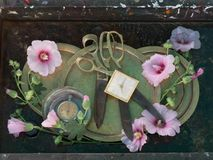 与葡萄酒项目的艺术静物画:有铜把柄的老古色古香的剪刀在精美桃红色花中的圆的盘说谎和 图库摄影