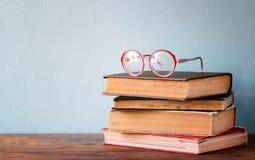 与葡萄酒玻璃的旧书在一张木桌上 减速火箭的被过滤的图象 免版税库存照片